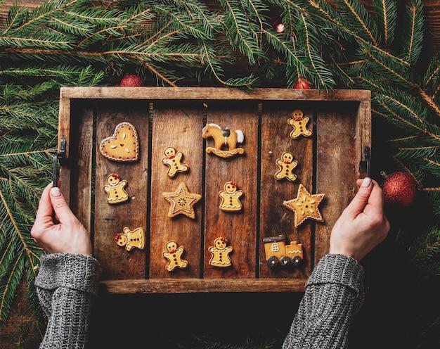 Vrouwelijke handen houden dienblad met koekjes naast kerstversiering