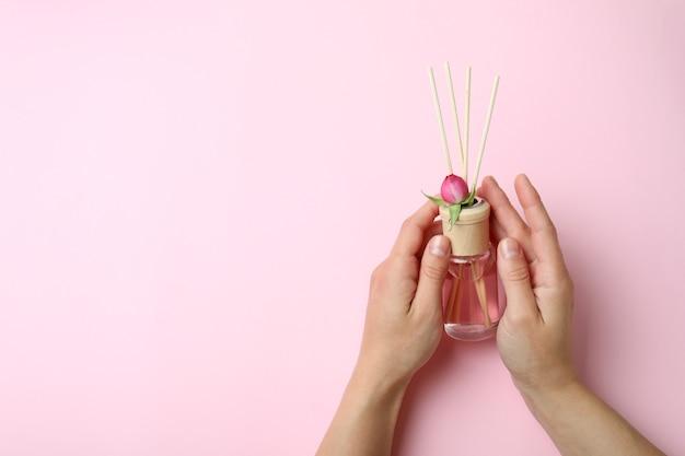 Vrouwelijke handen houden diffuser op roze achtergrond