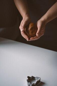Vrouwelijke handen houden een bal rauw gemberdeeg vast om te bakken kerstkoekjes