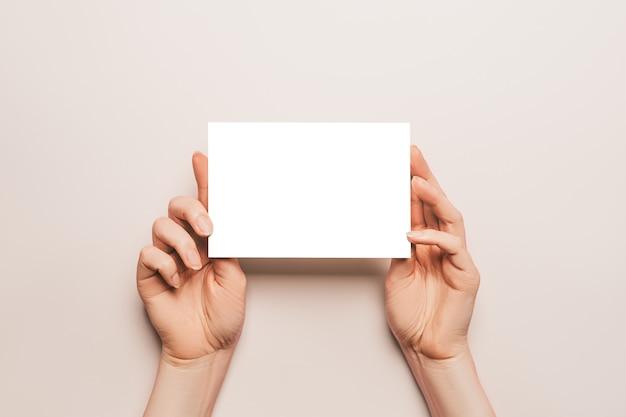 Vrouwelijke handen houden een blanco vel papier op een beige achtergrond. advertentie ruimte
