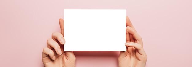 Vrouwelijke handen houden een blanco vel papier op een roze achtergrond. advertentie ruimte