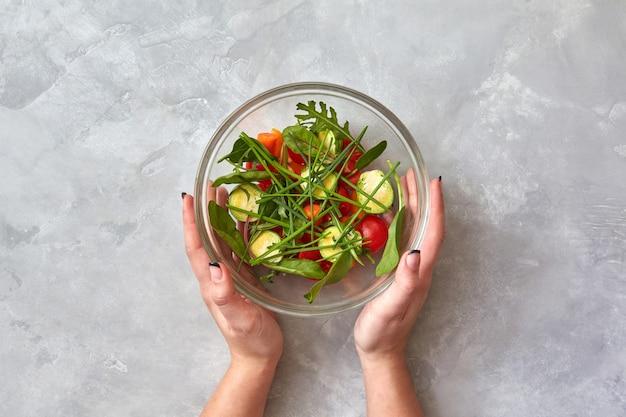 Vrouwelijke handen houden een bord met verse salade