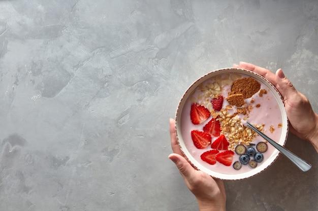 Vrouwelijke handen houden een bord met verse yoghurt, bessen en zelfgemaakte muesli