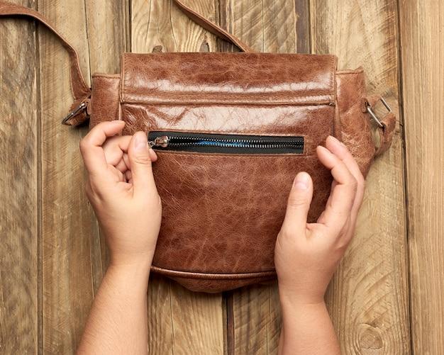 Vrouwelijke handen houden een bruine leren tas vast