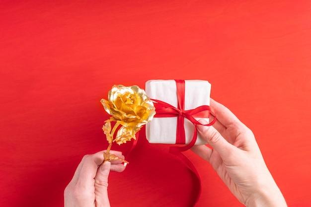 Vrouwelijke handen houden een cadeau verpakt in wit papier met een rood lint en een gouden roos