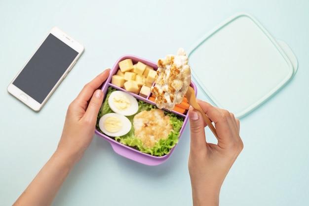 Vrouwelijke handen houden een container met gezond voedsel en een kippenkotelet op een vork vast. de mobiele telefoon ligt in de buurt