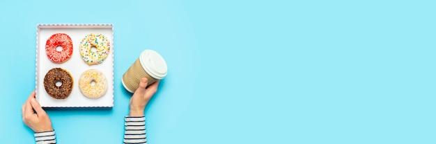 Vrouwelijke handen houden een doos met donuts, een kopje koffie op een blauw. concept zoetwarenwinkel, gebak, coffeeshop