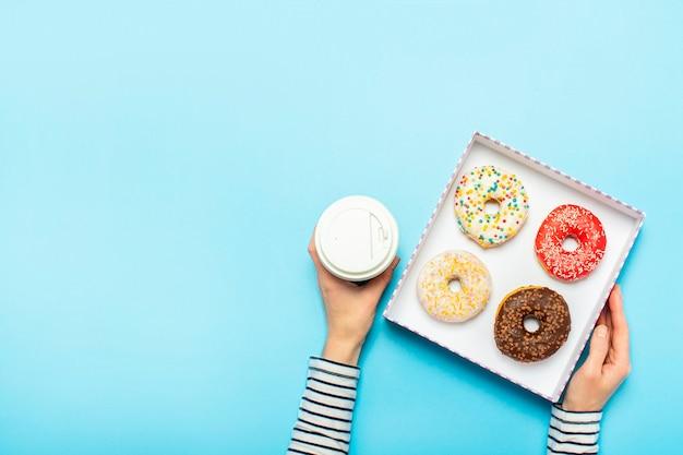 Vrouwelijke handen houden een doos met donuts, een kopje koffie op een blauw