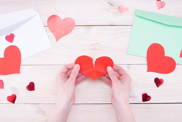 Vrouwelijke handen houden een gebroken hart met trouwringen op een houten tafel. huwelijksproblemen, echtscheiding