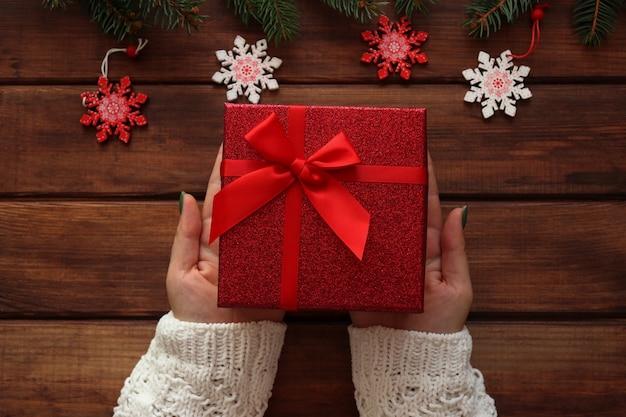 Vrouwelijke handen houden een geschenkdoos op houten tafel met kerstboomtakken en decoraties