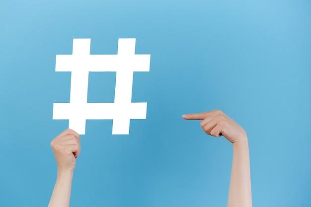 Vrouwelijke handen houden een groot groot wit hashtag-teken vast