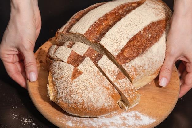 Vrouwelijke handen houden een houten bord met vers gebakken brood.
