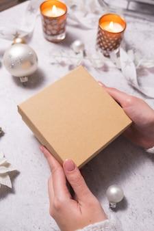 Vrouwelijke handen houden een kerstcadeaudoos vast. voorbereiding op kerst en oud en nieuw.