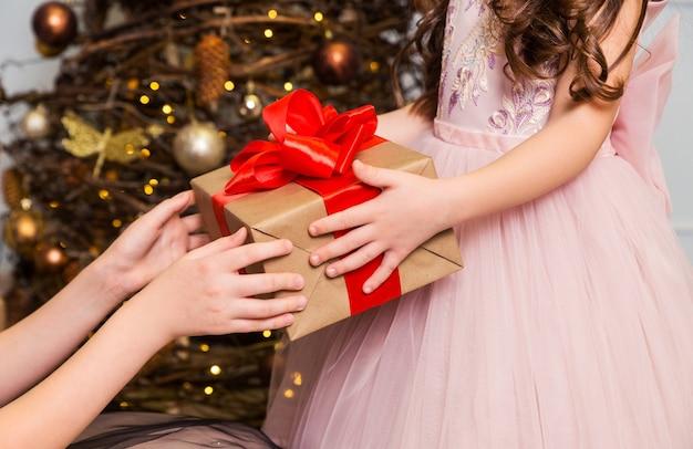 Vrouwelijke handen houden een klein meisje een geschenkdoos met een rode strik vast. horizontale foto