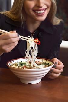 Vrouwelijke handen houden een kom met aziatische traditionele soep