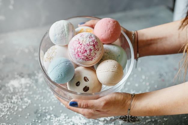 Vrouwelijke handen houden een kom vol met veelkleurige ballen voor een bad