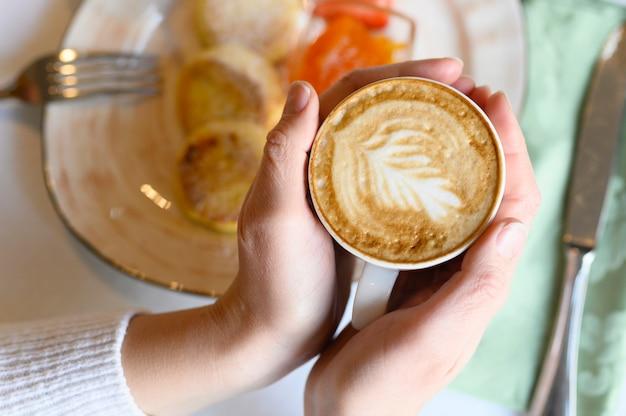 Vrouwelijke handen houden een kopje cappuccino met een prachtig patroon op het schuim op de achtergrond van de tafel met een bord met heerlijk eten. concept van ochtend ontbijt en brunch