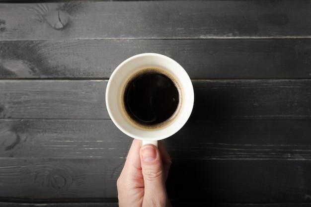 Vrouwelijke handen houden een kopje koffie op de houten tafel