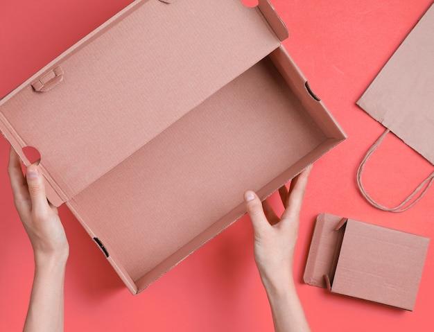Vrouwelijke handen houden een lege kartonnen doos op een roze met een papieren zak en een doos