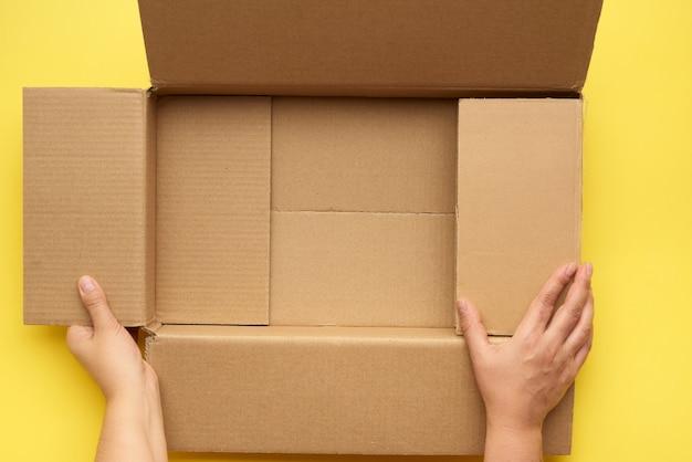 Vrouwelijke handen houden een lege open doos van bruin karton vast