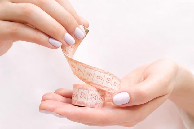 Vrouwelijke handen houden een meetlint vast. slank lichaam en dieetconcept
