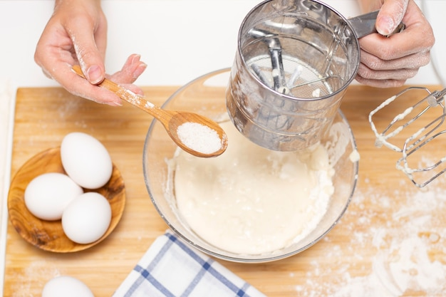 Vrouwelijke handen houden een mixer vast om deeg te mengen