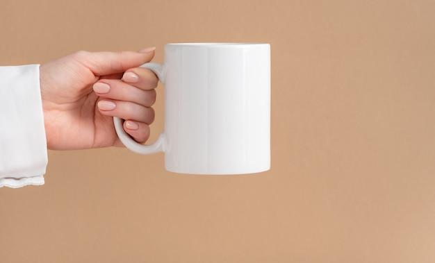 Vrouwelijke handen houden een mockup van een witte lege mok of kopje koffiethee vast