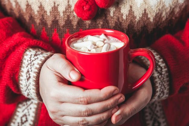 Vrouwelijke handen houden een mok cacao met marshmallow vast