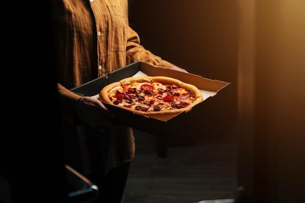 Vrouwelijke handen houden een mooie smakelijke pepperoni pizza voor de deur