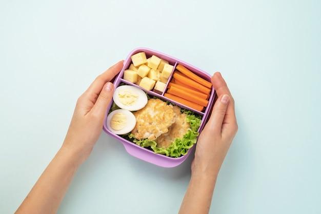 Vrouwelijke handen houden een plastic lunchbox met lunch vast