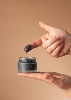 Vrouwelijke handen houden een potje zwarte cosmetische gezichtsverzorgingscrème vast en passen deze op de vinger toe