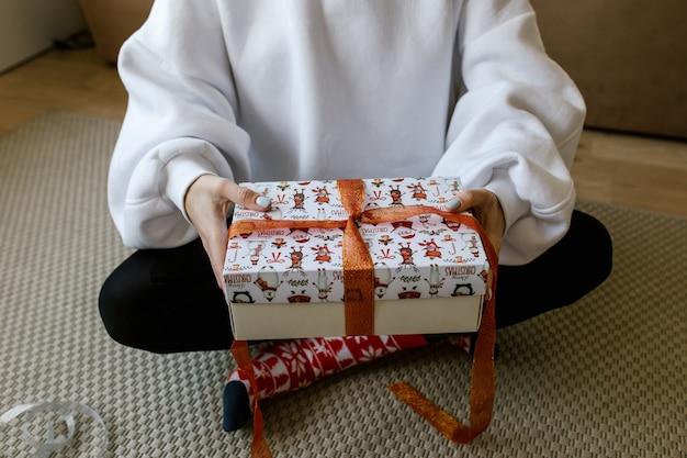 Vrouwelijke handen houden een rode en gouden glanzende strik op een geschenkdoos. vrouw die een feestelijk verrassingscadeau inpakt. kerst- of nieuwjaarsgeschenk met een rood lint. voorbereiding op kerstvakantie.