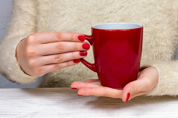 Vrouwelijke handen houden een rode kop tegen de achtergrond van een witte pluizige trui met rode manicure