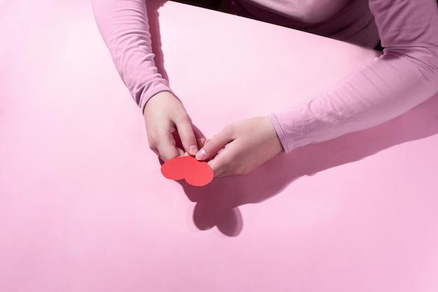 Vrouwelijke handen houden een rood hart vast, close-up. valentijnsdag. modern concept.