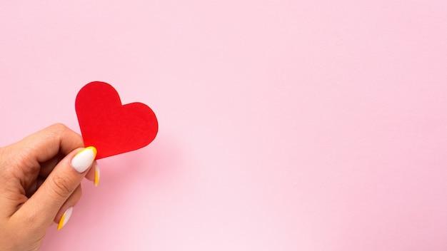Vrouwelijke handen houden een rood hart vast