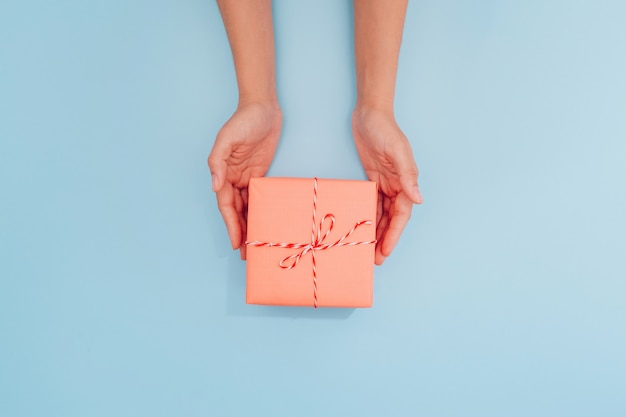 Vrouwelijke handen houden een roze geschenkdoos met een dun lint als cadeau voor kerstmis, nieuwjaar, moederdag of verjaardag op een blauwe tafel achtergrond, bovenaanzicht. plaats voor tekst.