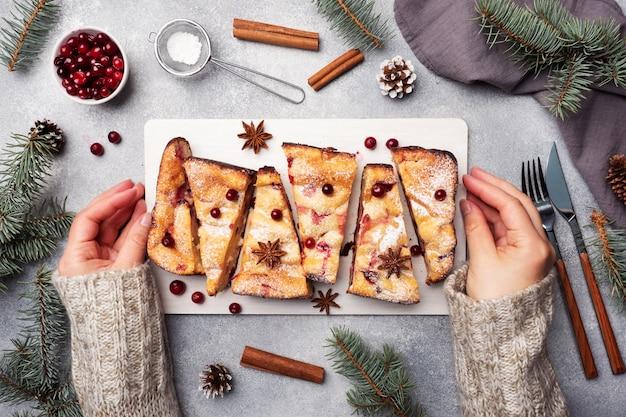 Vrouwelijke handen houden een standaard met een cottage cheese taart ovenschotel met veenbessen en kruiden bestrooid met poedersuiker. grijze betonnen tafel.