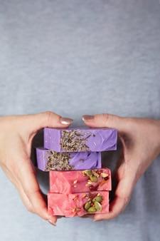 Vrouwelijke handen houden een stapel zelfgemaakte handgemaakte zeep. het aroma van kersen en lavendel. kleine bedrijven, biologische producten, natuurlijke ingrediënten.