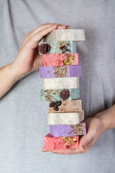 Vrouwelijke handen houden een stapel zelfgemaakte handgemaakte zeep. kleine bedrijven, biologische producten, natuurlijke ingrediënten.