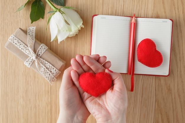 Vrouwelijke handen houden een stuk speelgoed hart voor valentijnsdag