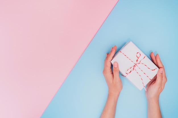 Vrouwelijke handen houden een witte geschenkdoos met een dun lint als cadeau voor kerstmis, nieuwjaar, moederdag of verjaardag op een diagonale blauwe en roze tafel achtergrond, bovenaanzicht. plaats voor tekst.