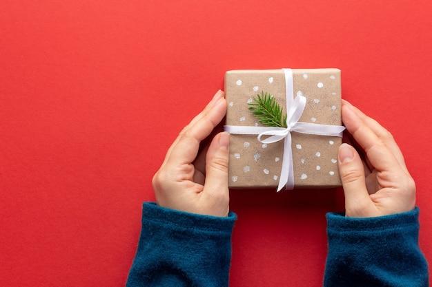 Vrouwelijke handen houden eenvoudige kerstcadeau met wit lint op rood