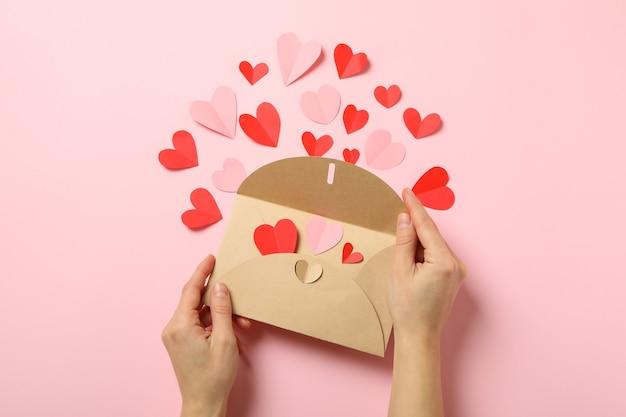 Vrouwelijke handen houden envelop op roze achtergrond met decoratieve harten