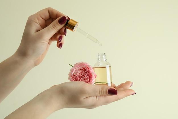 Vrouwelijke handen houden etherische olie van rozen op beige