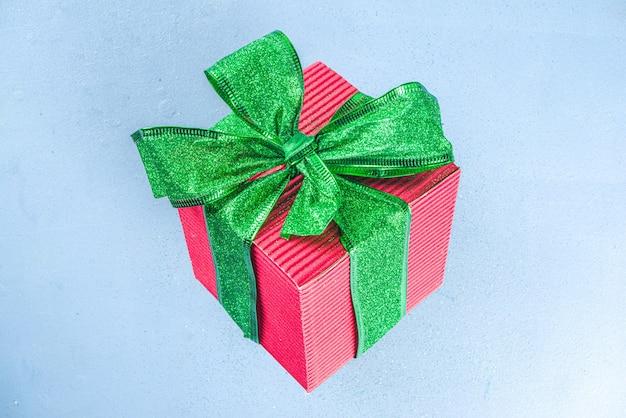 Vrouwelijke handen houden grote rode geschenkdoos glinsterende groene gebonden strik op lichtblauwe achtergrond, kopieer ruimte. meisjeshanden met huidige doos. kerstmis, nieuwjaar wintervakantie verjaardagscadeau