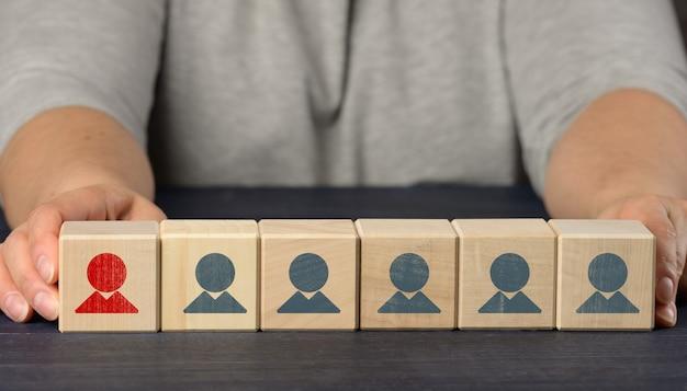 Vrouwelijke handen houden houten kubussen met beeldjes vast. zoekconcept voor medewerkers, personeelswerving. selectie van getalenteerde en unieke medewerkers voor loopbaanontwikkeling