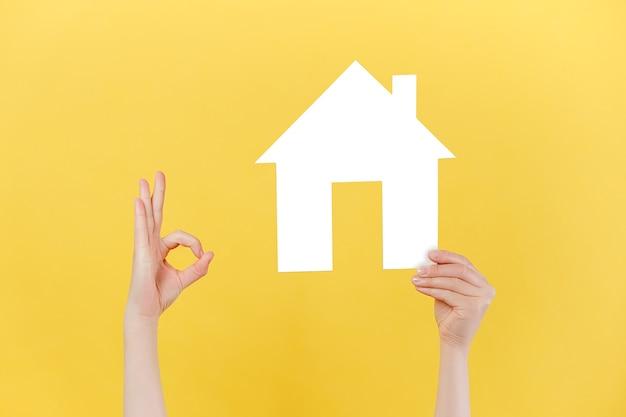 Vrouwelijke handen houden huismodel vast en maakt een goed gebaar