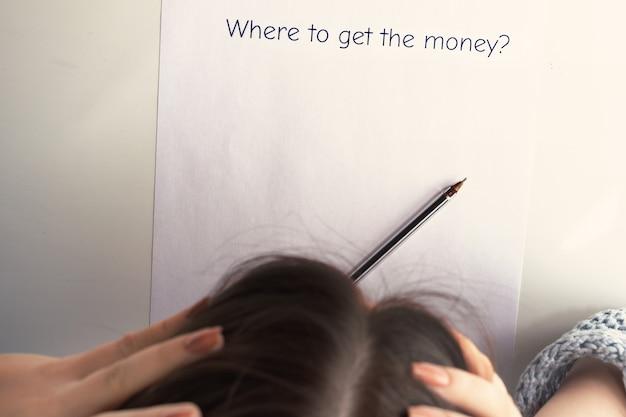 Vrouwelijke handen houden hun hoofd boven een vel papier met de inscriptie waar ze geld kunnen krijgen