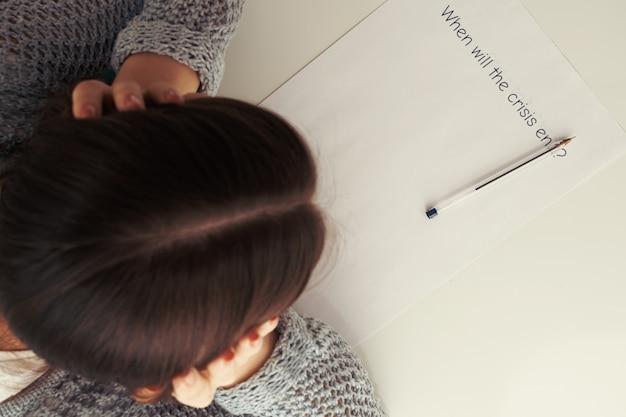 Vrouwelijke handen houden hun hoofd boven een vel papier met de inscriptie wanneer de crisis zal eindigen