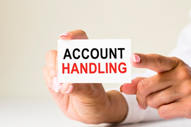 Vrouwelijke handen houden kaartpapier vast met de tekst account handling op een witte lichte achtergrond. zakelijk en financieel concept